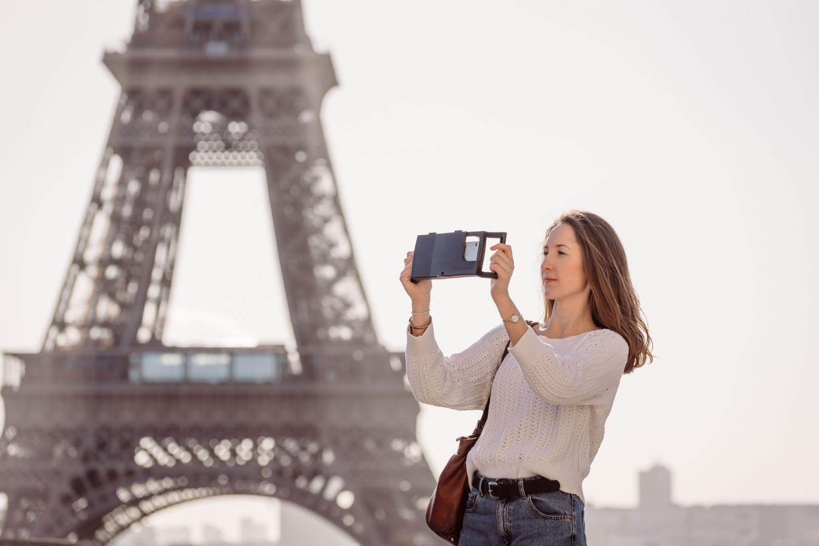 lifestyle product photoshoot in Paris France for iOgrapher, model in front of the Eiffel tower holding iPhone filming case