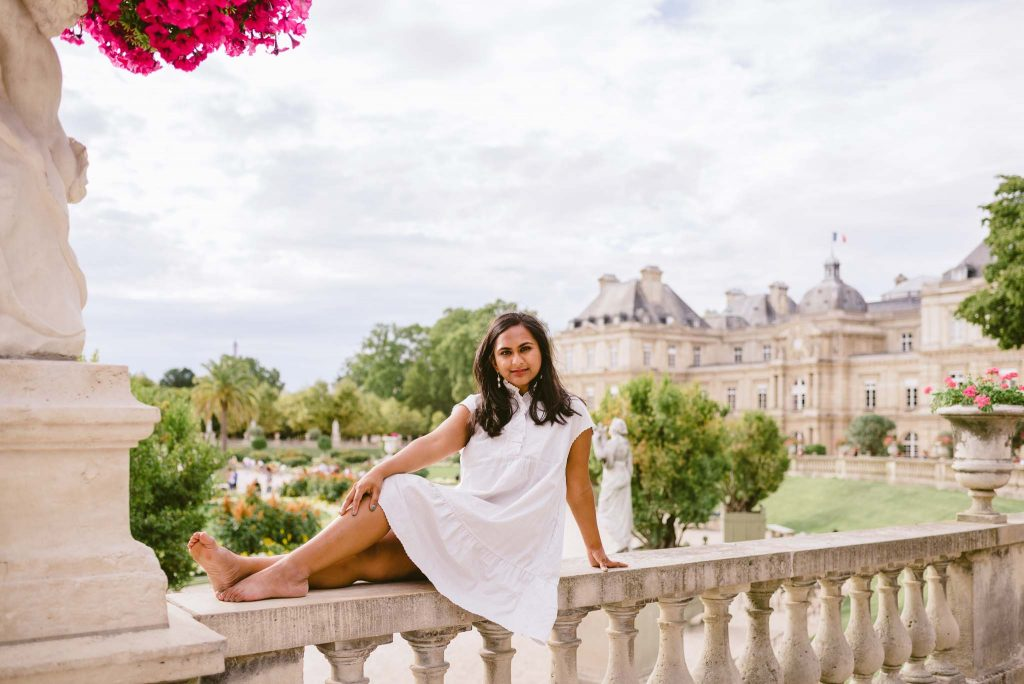 Lifestyle portrait photography session in Paris—young Indian woman barefoot in a short white dress sitting on stone railing in the Luxembourg gardens with the Luxembourg Palace in the background in summertime.