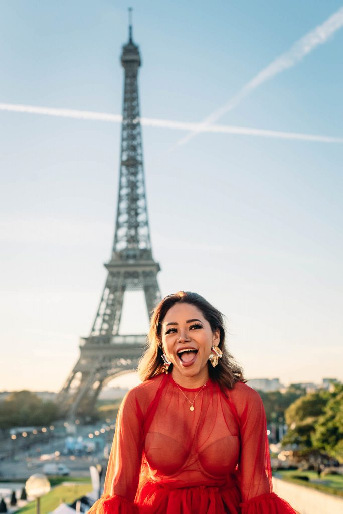 Fun photoshoot in front of the Eiffel Tower in a sheer red dress and glam earrings