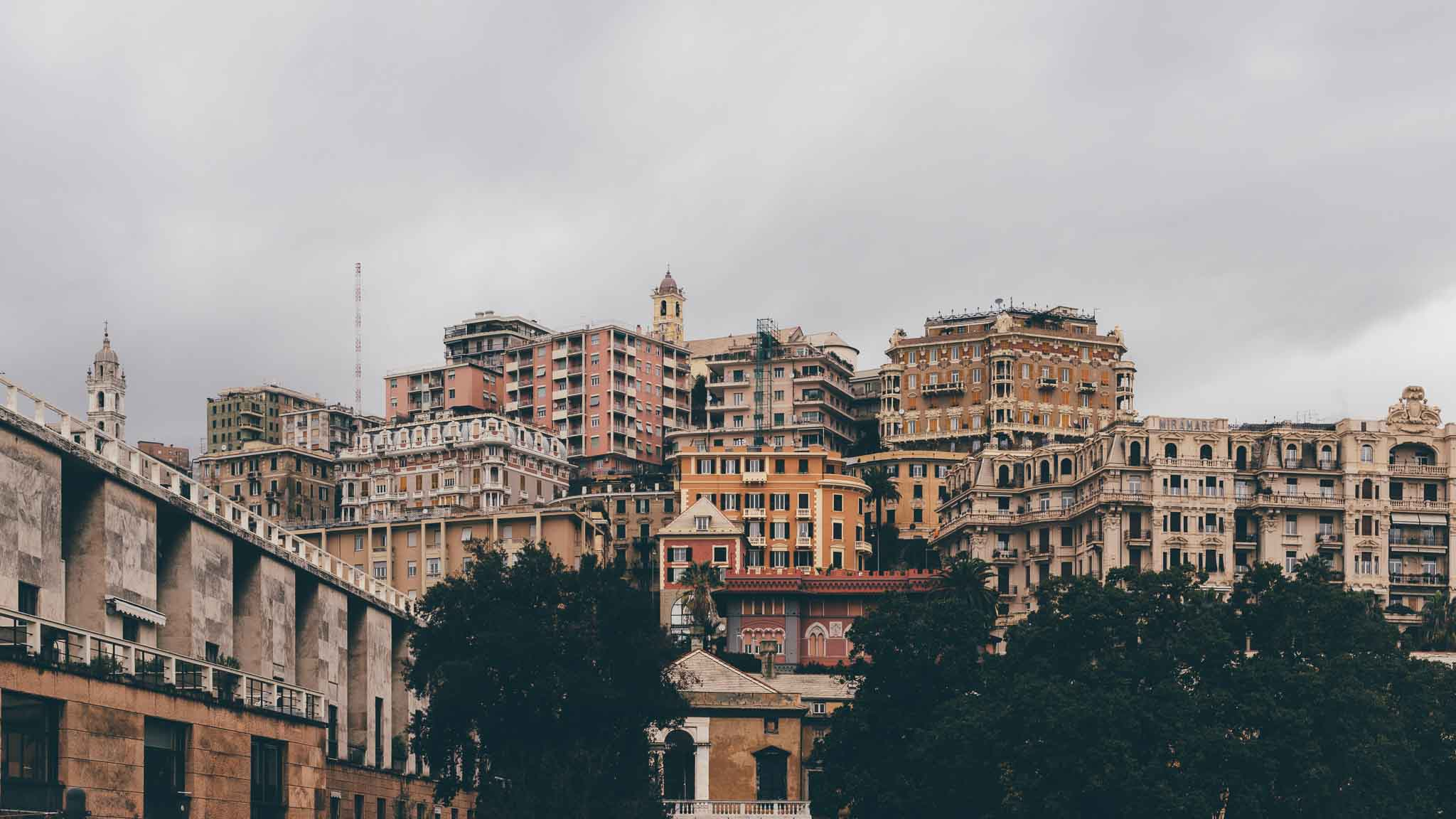 Moody photo of orange and pink buildings on the hillside by Genova, Italy on a cloudy day