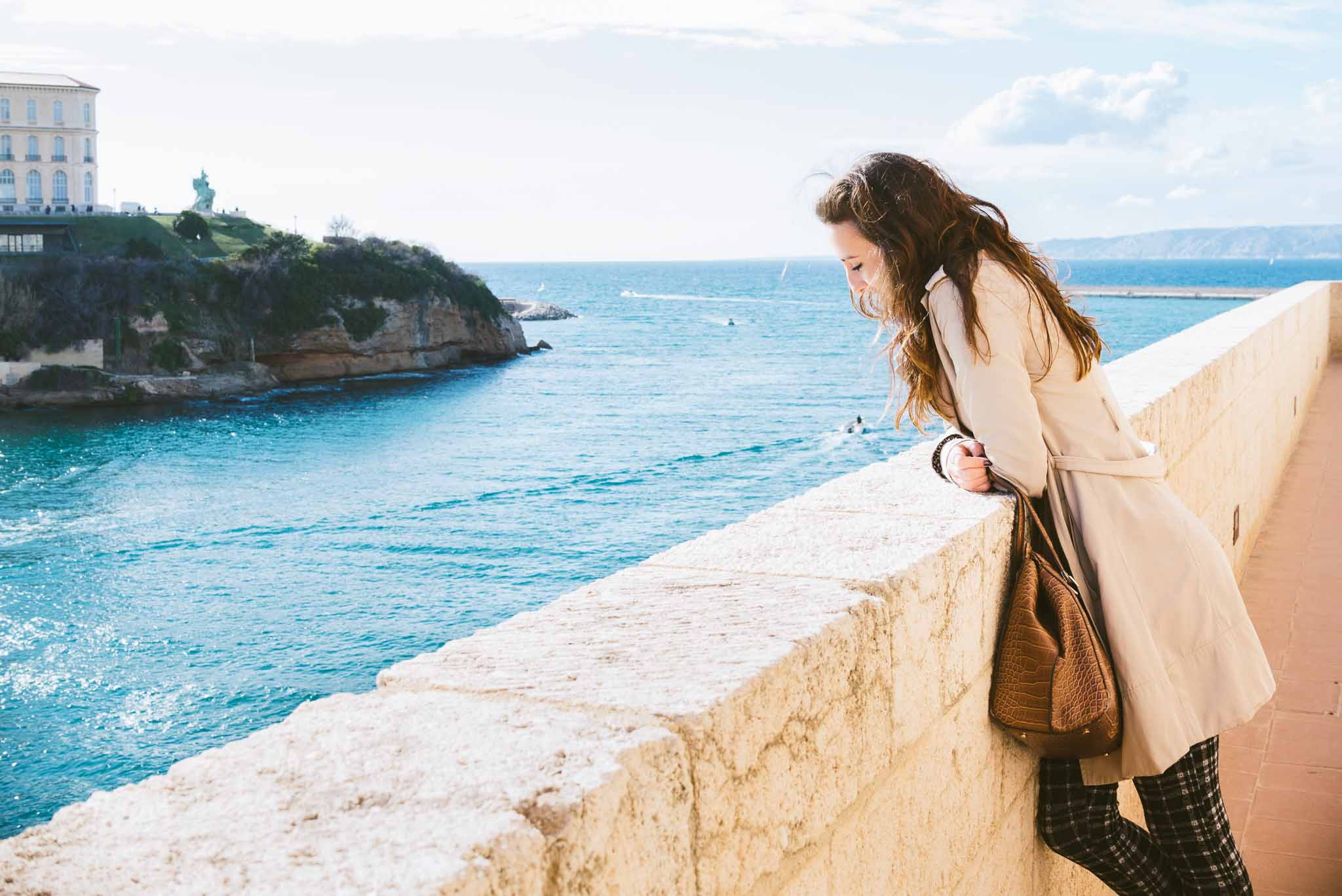 Fashion photography image of a brunette woman in a trench coat, black and grey plaid pants and brown purse looking out at the Mediterranean sea over a stone wall in Marselle, France.