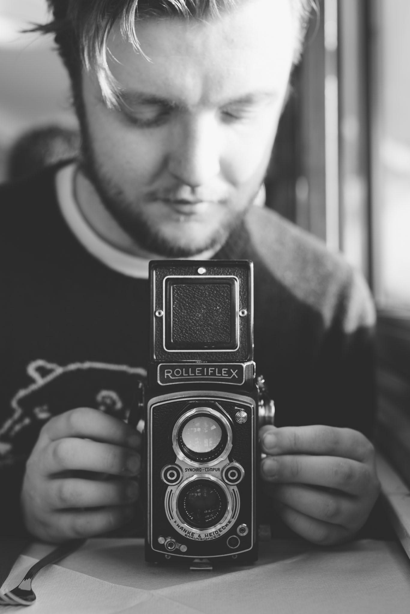 Black and white portrait photography of man holding a medium format rolleiflex camera