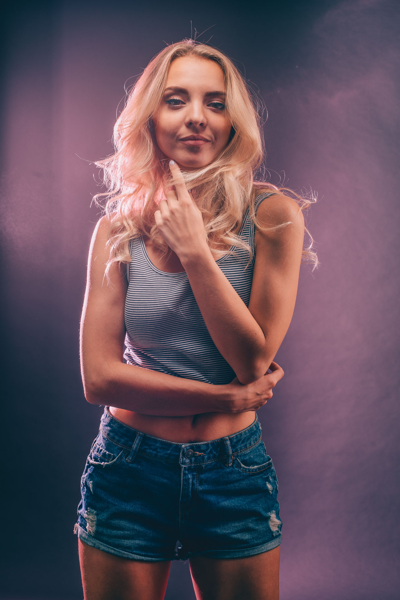 Studio photography shot of model Anna Hrehlevych in a crop top and jean shorts against a navy and pink background