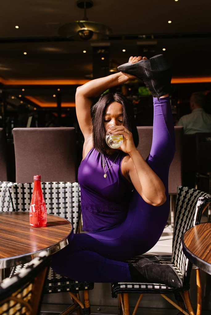 yoga photography in a paris cafe with a woman doing a half split and drinking sparkling water