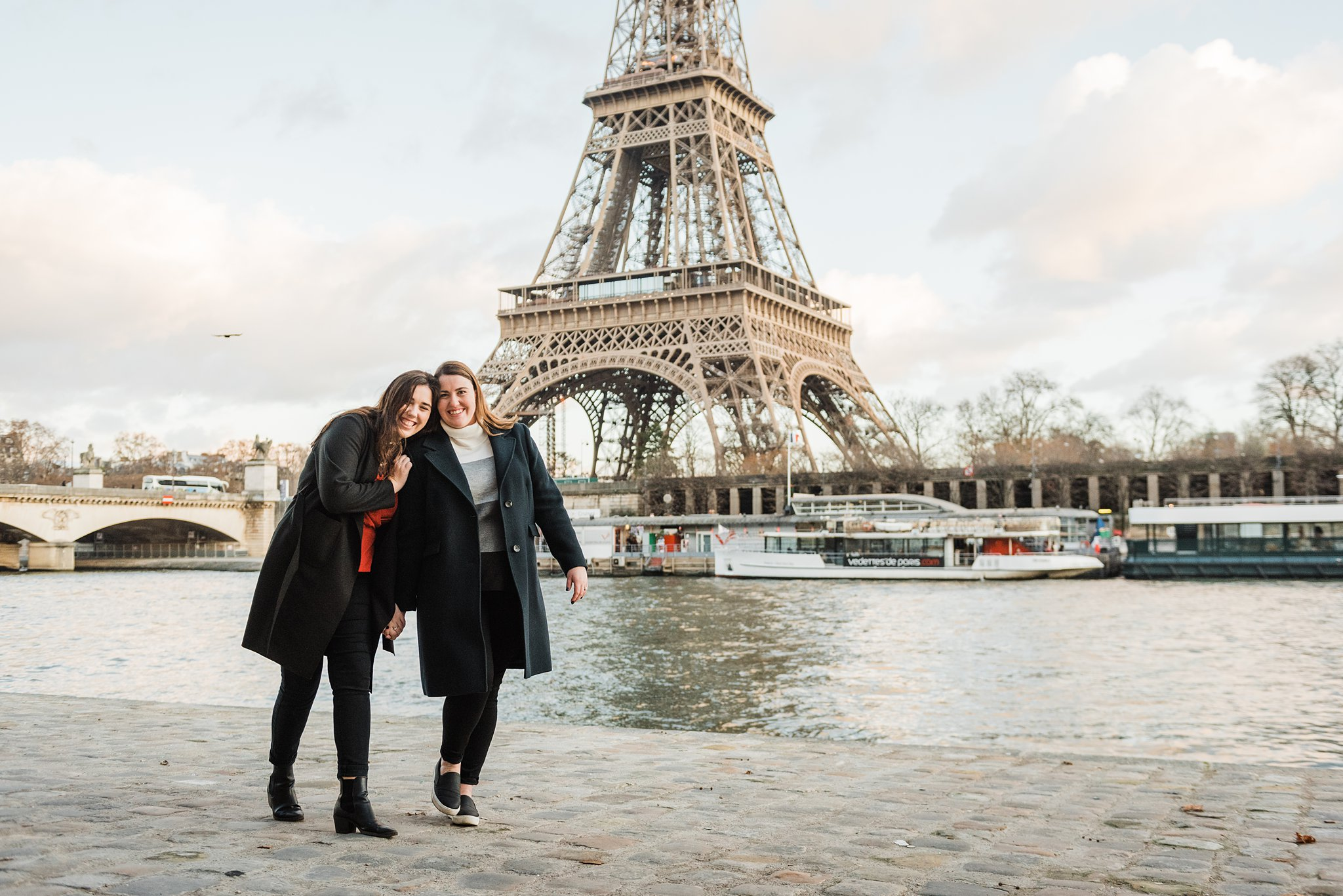Sisters by the Seine river during a December photo shoot in Paris, as a study abroad activity and Christmas gift