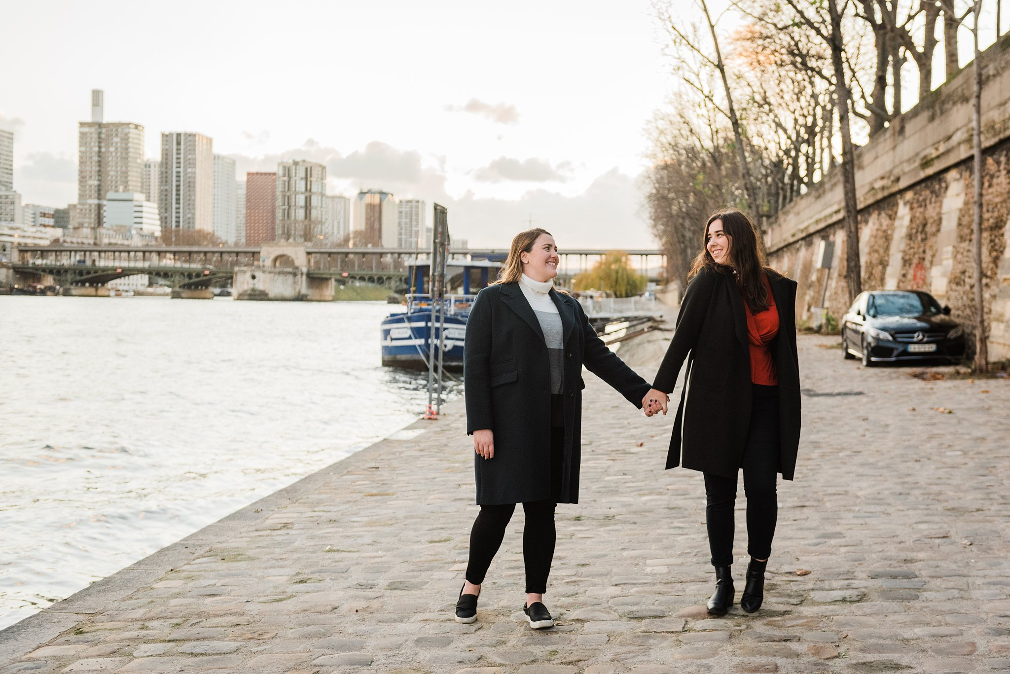 Two sisters holding hands and looking at each other by the Seine River in Paris, during a professional photo shoot