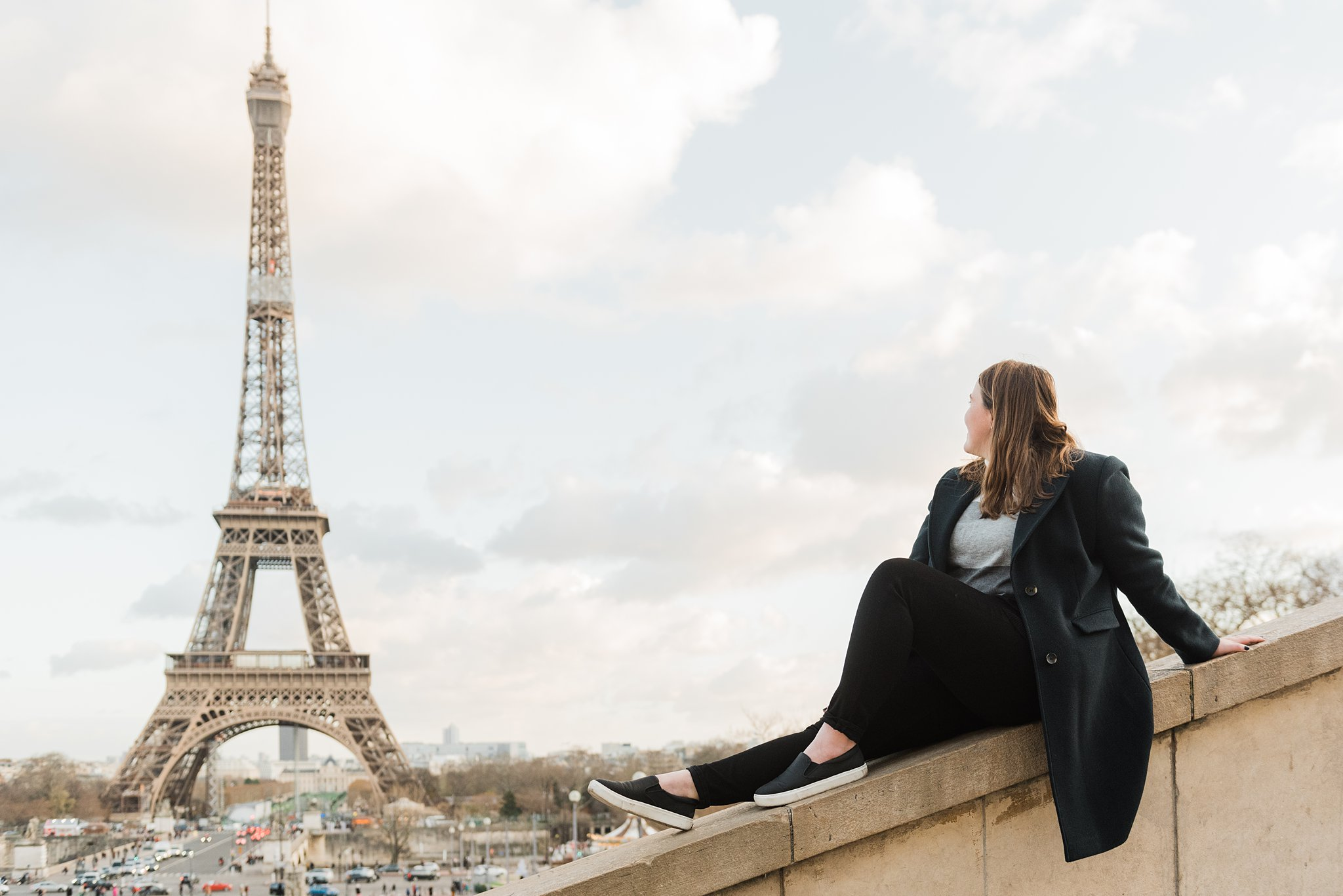 Woman sitting on ledge looking at the Eiffel Tower during a winter photo shoot in Paris