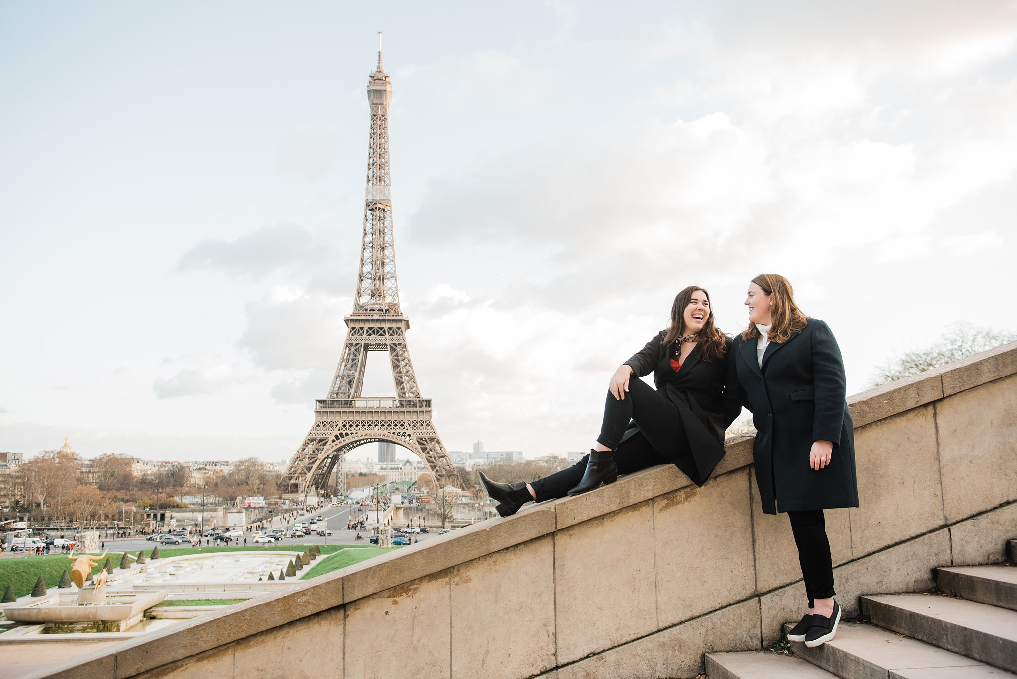 Two sisters laughing on staircase in Trocadero with the Eiffel Tower in the background, during a winter photo shoot in Paris they did as a study abroad activity and Christmas gift