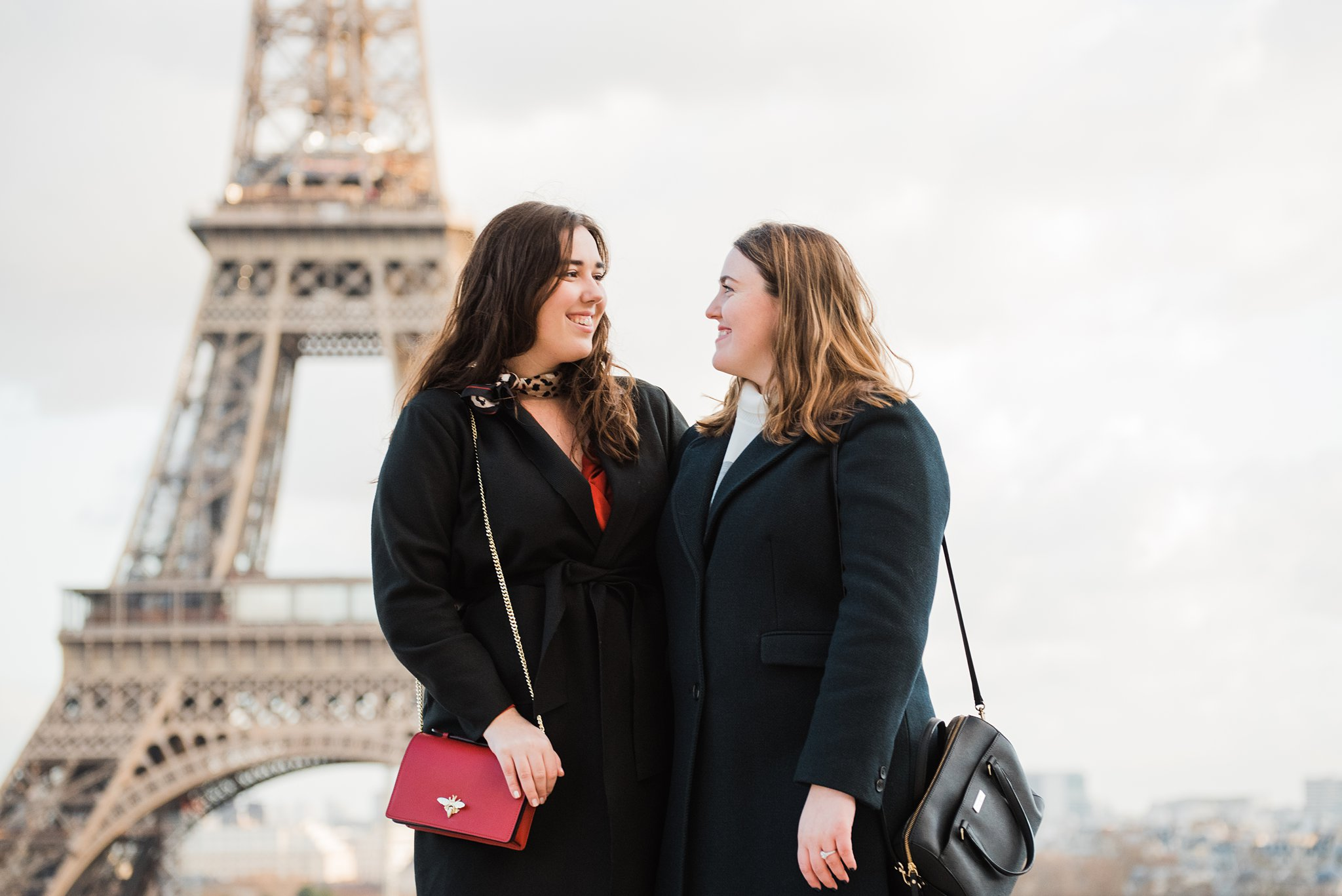 Closeup of sisters looking at each other in front of the Eiffel Tower on a winter photo shoot in Paris