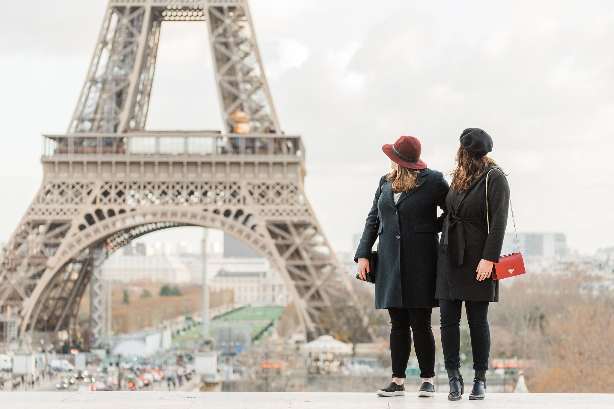 Two sisters in hats looking at the eiffel tower on a winter photo shoot in Paris, as a study abroad activity and Christmas gift