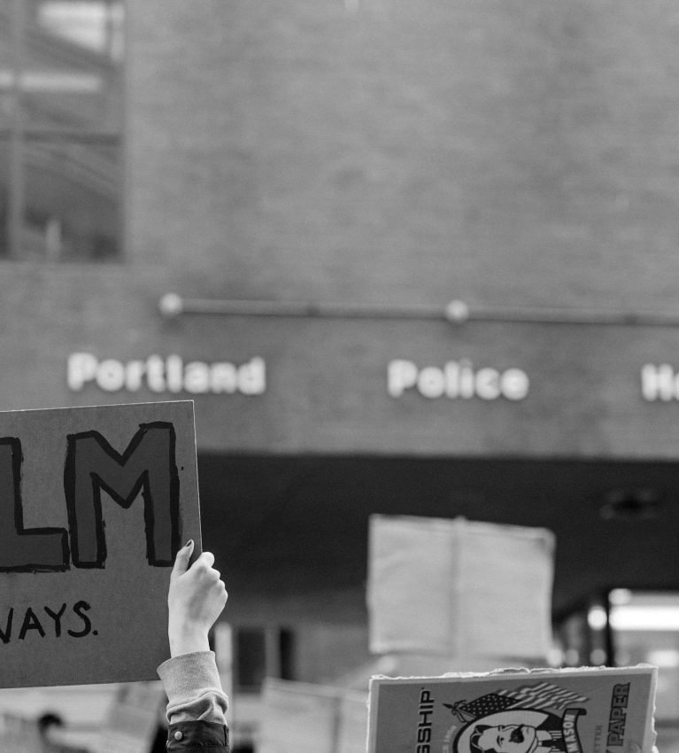 """black and white photo of hands holding up a protest sign saying """"BLM always"""" in front of Portland, Maine police station"""