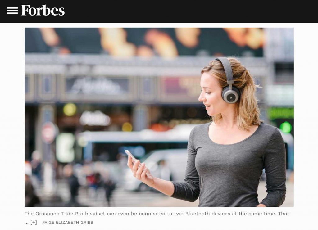 Screenshot of Paige Elizabeth Gribb's photo featured on Forbes.com: lifestyle product photography of model wearing headphones and talking on the phone on a busy Paris street